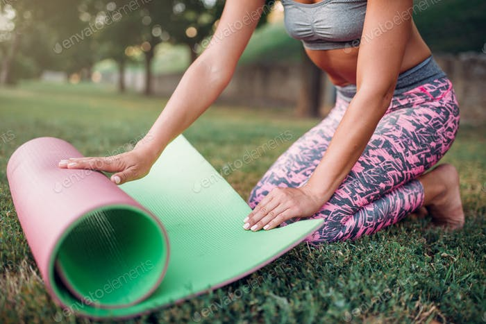 Young woman rolling yoga mat in park