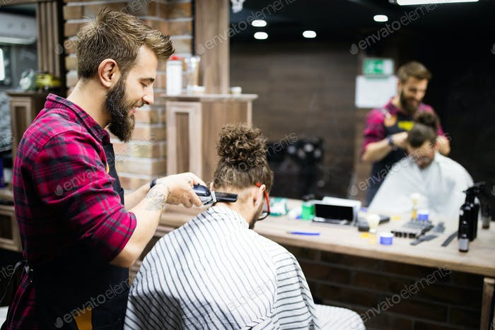 Man having a haircut with a hair clippers in barbershop salon