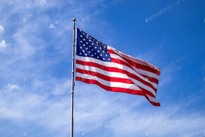 United States flag on a pole waving on blue sky background.
