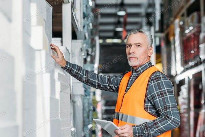 senior worker using digital tablet in storehouse