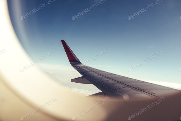 An airplane wing through airplane window with blue sky background