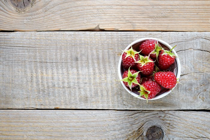 Raspberries in bowl on wooden table top view
