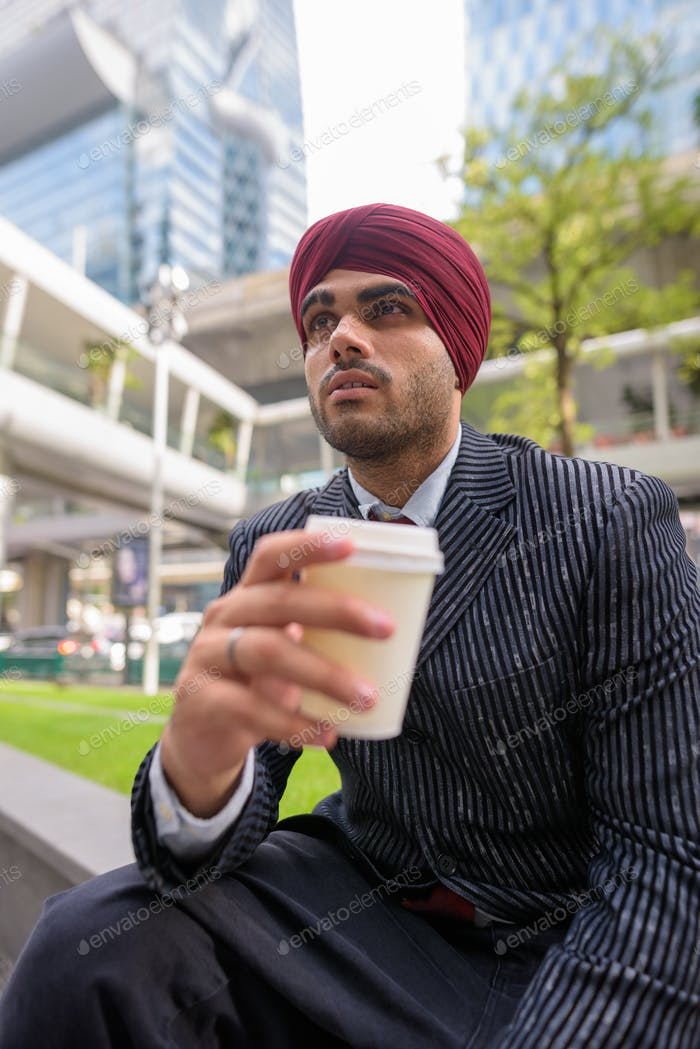 Indian businessman sitting outdoors in city while having coffee break