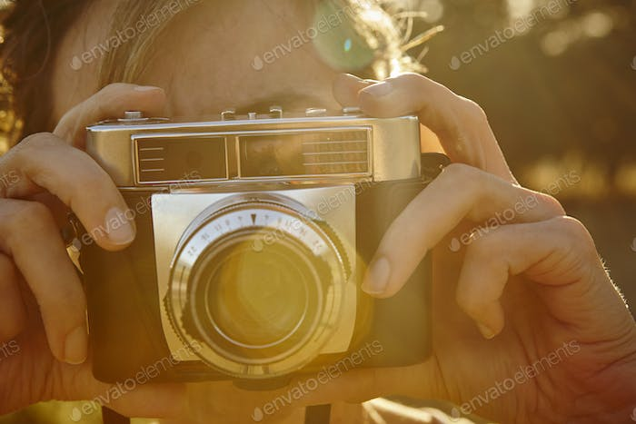 Woman taking pictures with vintage camera. Travel background.