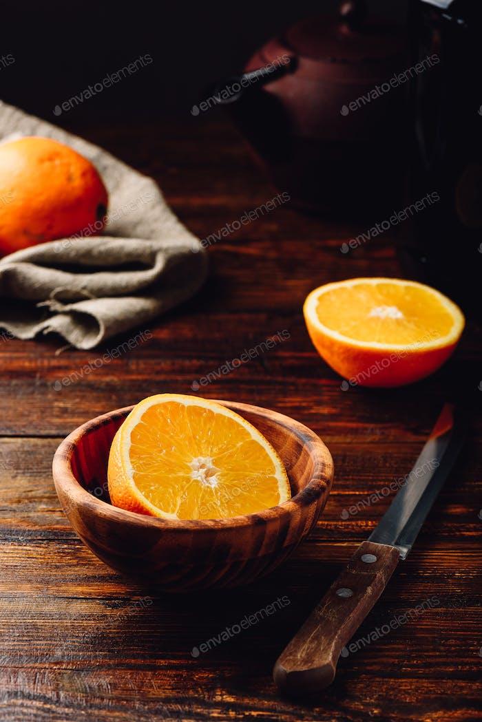 Half of orange in a wooden bowl