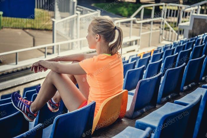 Blonde weiblich sitzt auf Plastiksitz.
