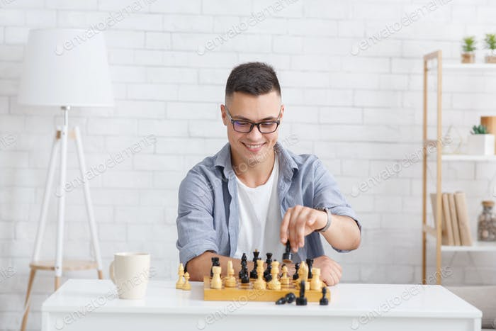 Self-isolation, online education concept. Cheerful guy plays in chess online with virtual partner