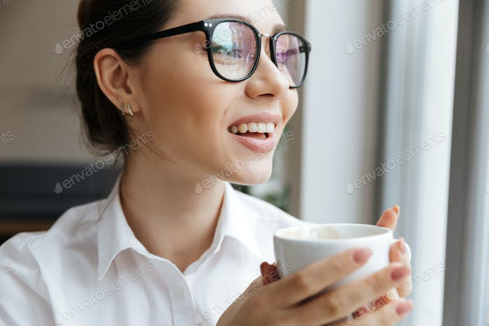 Cheerful business woman sitting indoors drinking coffee