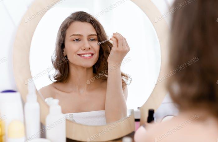 Junge Frau Anwendung kosmetischen Serum im Badezimmer