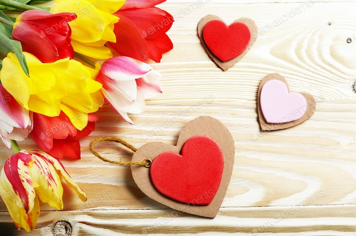Colorful tulip flowers and heart shape cards on wooden table bac
