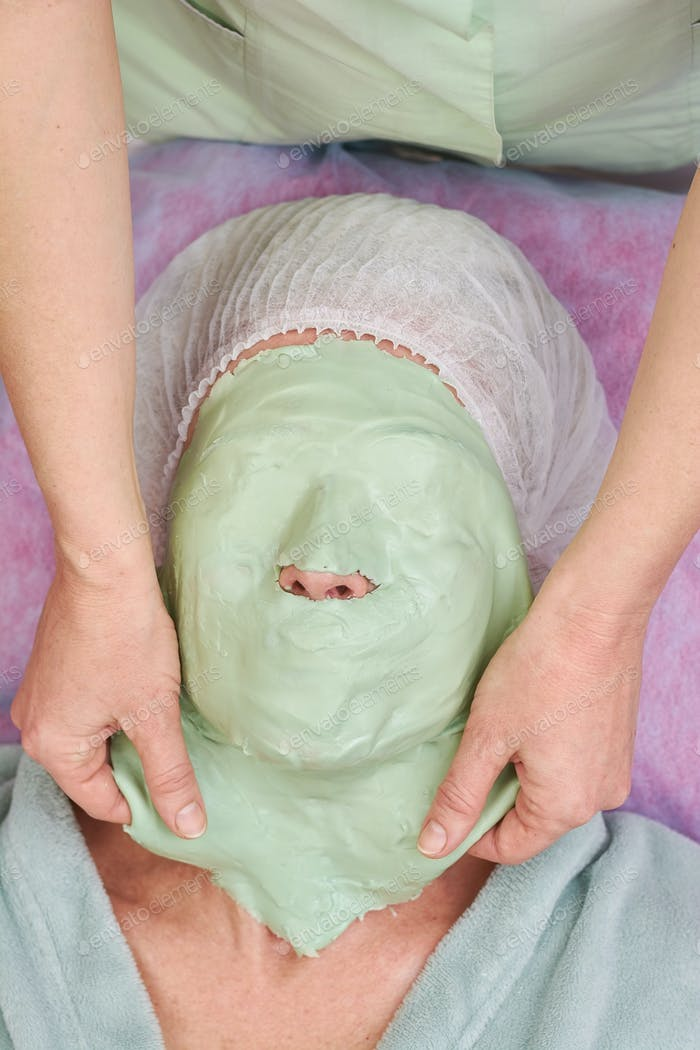 Hands removing facial mask