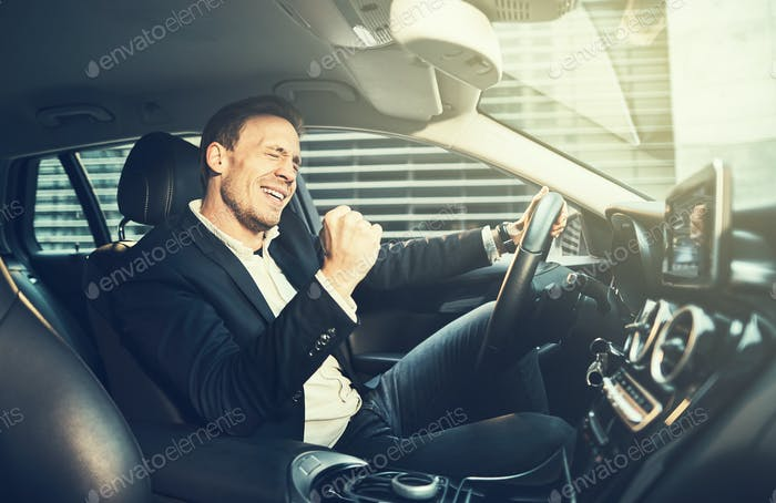 Businessman fist pumping while driving in his car in the city