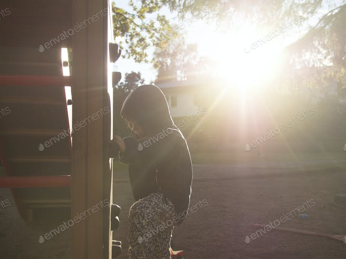 Girl playing at playground during sunny day