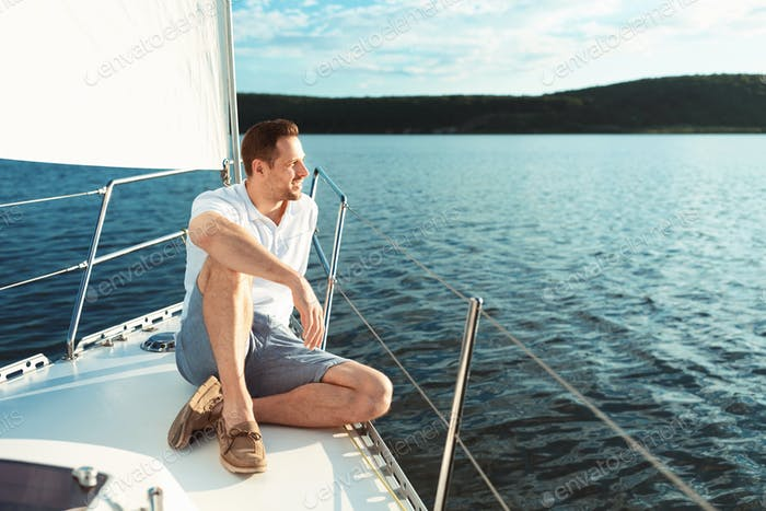 Man Relaxing Sitting On Sailboat Deck Spending Summer Day Outside
