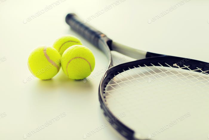 close up of tennis racket with balls