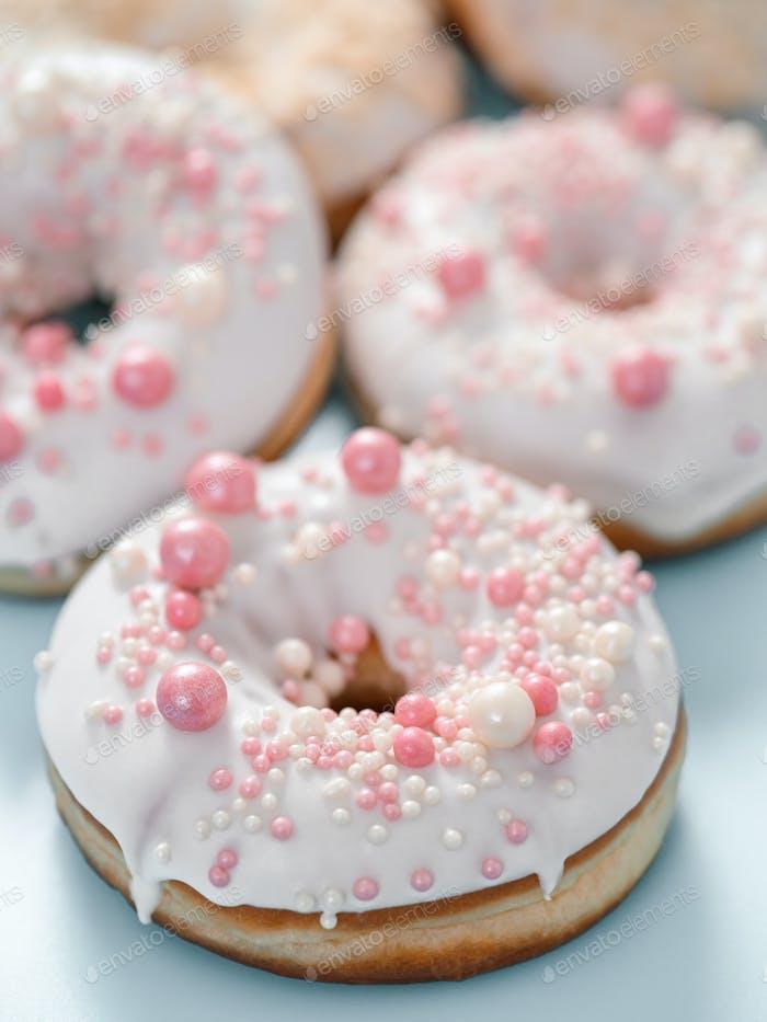 Donuts glaseados románticos. Esmalte blanco, aderezo rosa