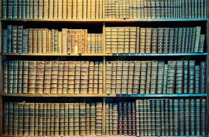 Vintage toned old books on wooden shelves.
