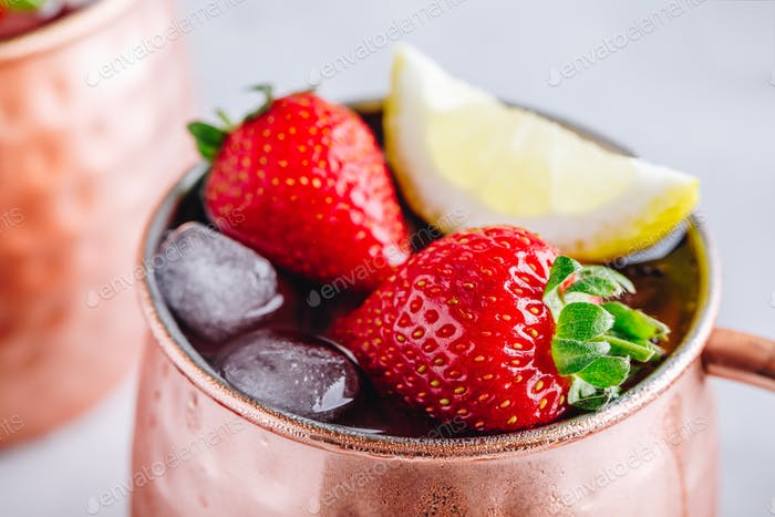 Erfrischender eisiger Moskauer Maultier alkoholischer Cocktail in Kupfertassen mit Erdbeere und Zitrone