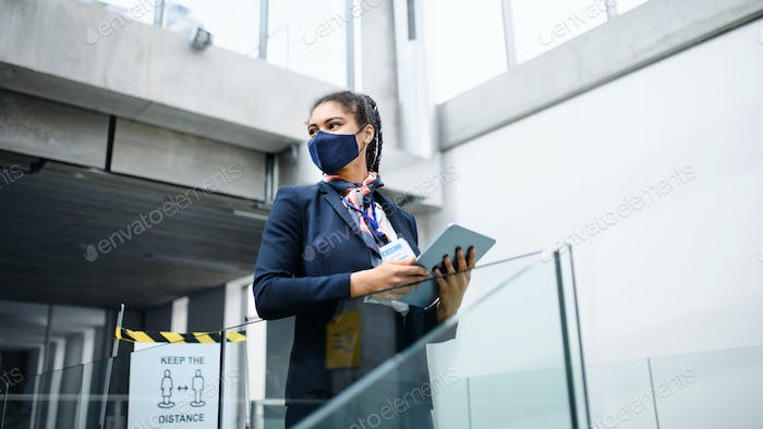 Young air hostess in airport lounge, coronavirus, travel and new normal