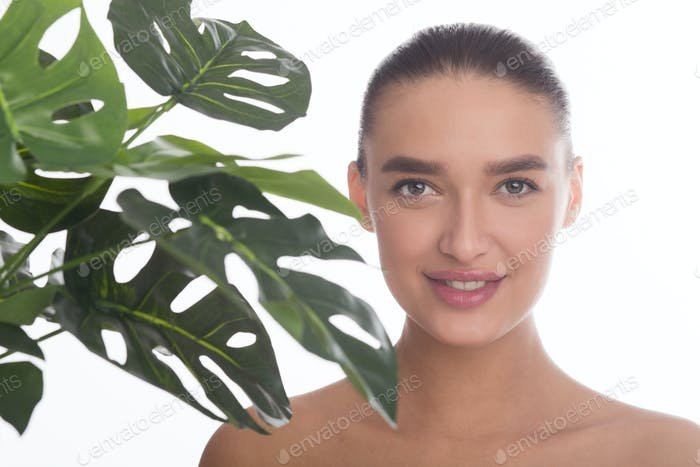 Calm girl with green palm leaf near her face