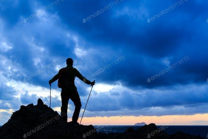 Hiking silhouette backpacker looking at sunset ocean
