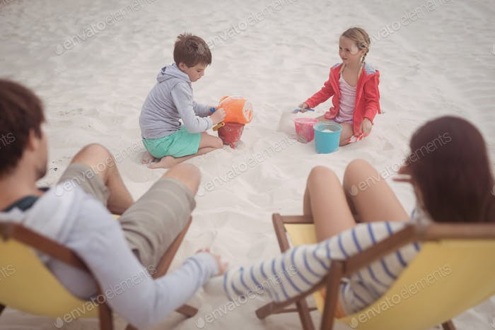 Siblings playing by parents relaxing on launge chairs at beach