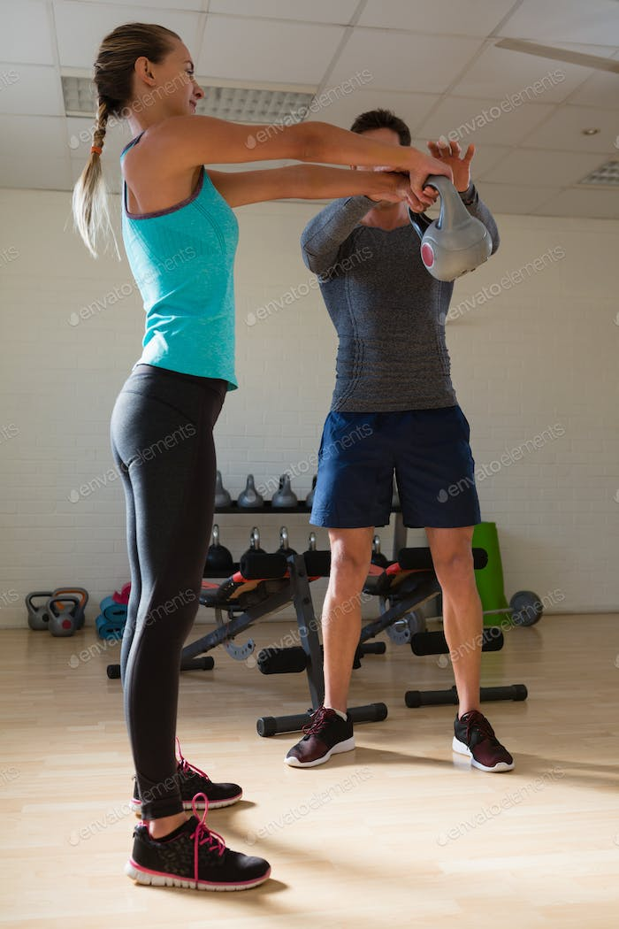 Male trainer training woman in lifting kettlebells