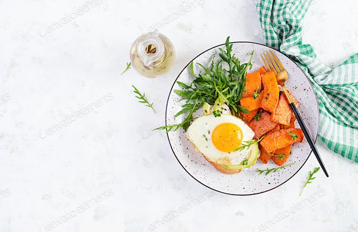 . Avocado sandwich with fried egg and fried sliced pumpkin with arugula