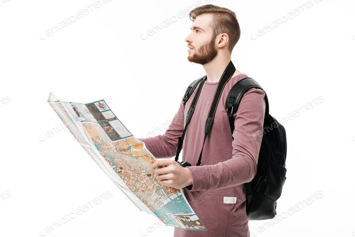 Young man dreamily looking aside with open map in hands and backpack on white background