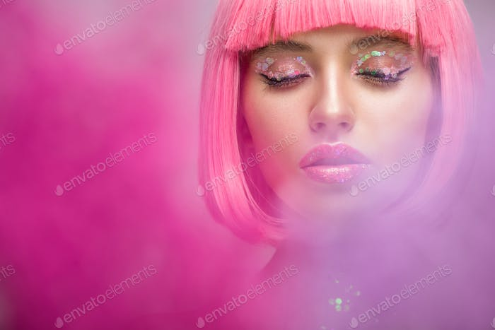 attractive woman with pink hair and makeup with glitter standing in pink smoke with closed eyes