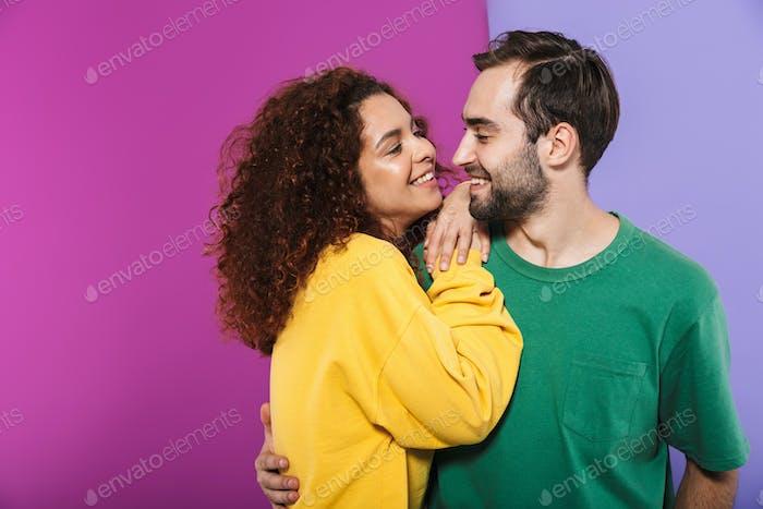 Porträt von attraktiven glücklichen Paar Mann und Frau in bunten Kleidung lächelnd und umarmt zusammen