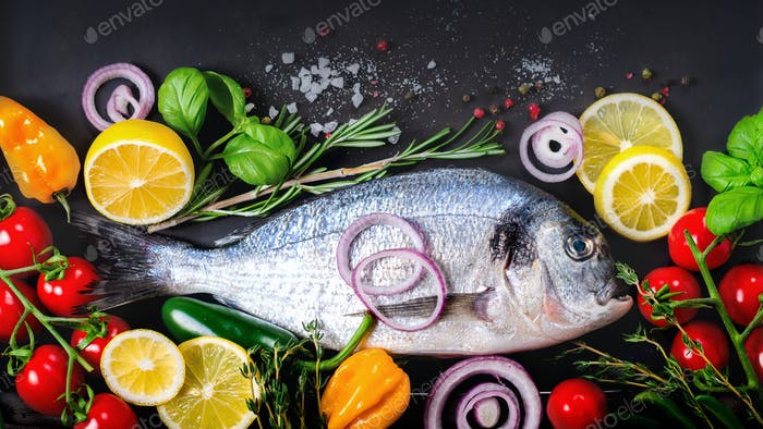 Fresh uncooked fish, dorado, sea bream with lemon, herbs, vegetables and spices on stone background