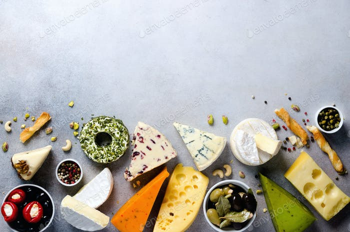 Assortment of hard, semi-soft and soft cheeses with olives, grissini bread sticks, capers, grape, on