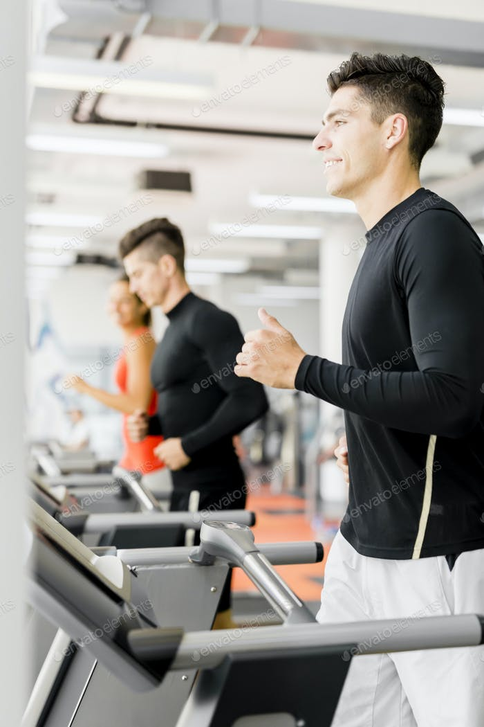 Group of young people using treadmills in a gym
