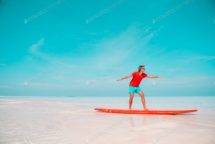 Happy young surf man on red surfboard at the sea