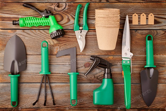 Gardening tools on wooden background flat lay