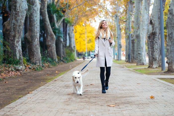 Attractive young woman walking with her lovely dog in the park in autumn.
