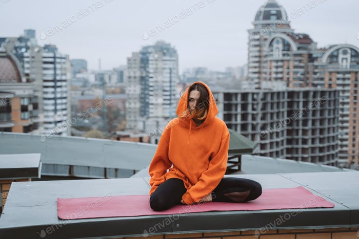 Woman practicing yoga on the mat on the roof and doing yoga exercises