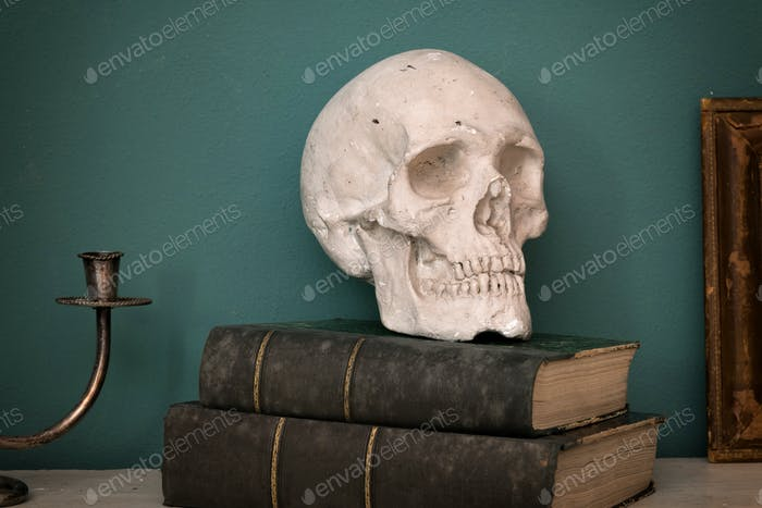 Replica of a human skull on vintage books