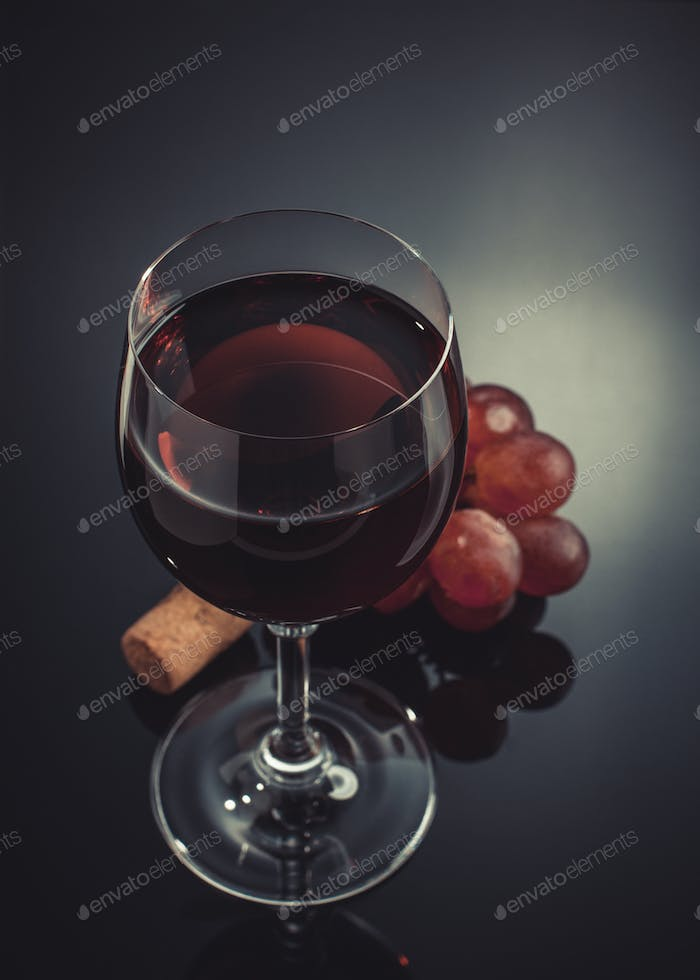 wine glass and grapes on black