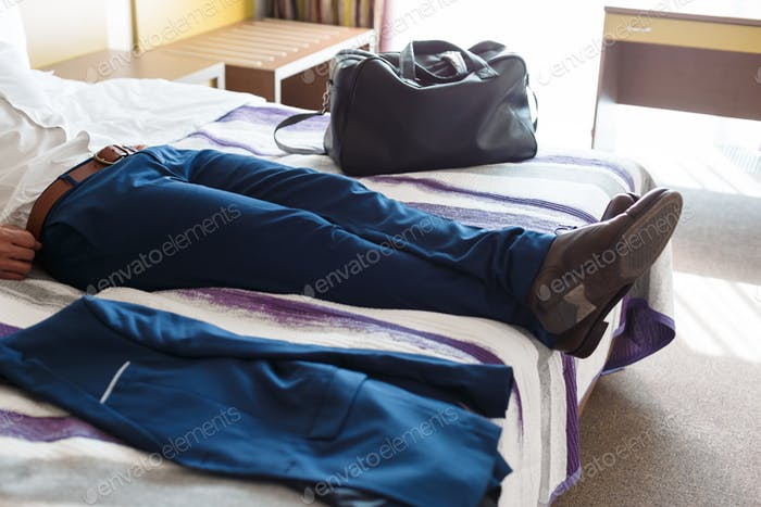 Man legs in formal trousers on hotel bed