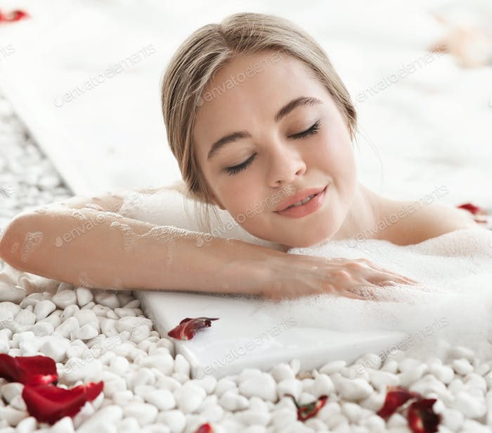 Portrait of delightful young woman with closed eyes enjoying bath