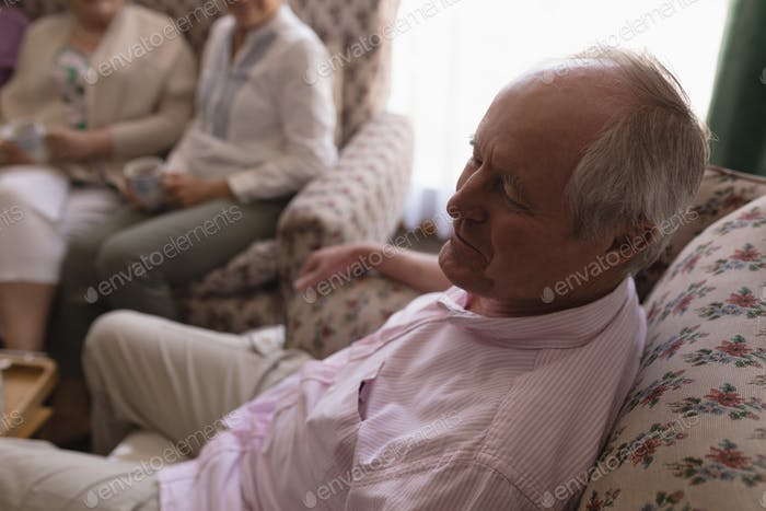 Side view of active senior man relaxing in living room on sofa at home