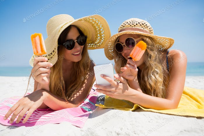 Female friends using smart phone while eating popsicles