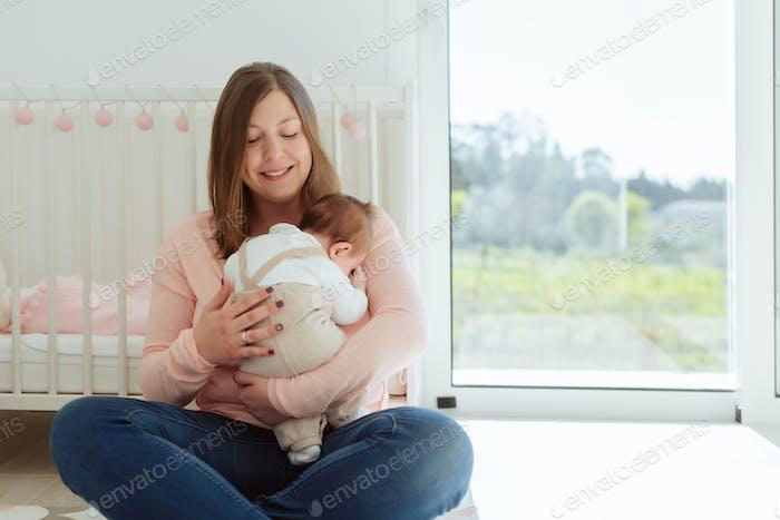 Junge Mutter hält neugeborenes Baby