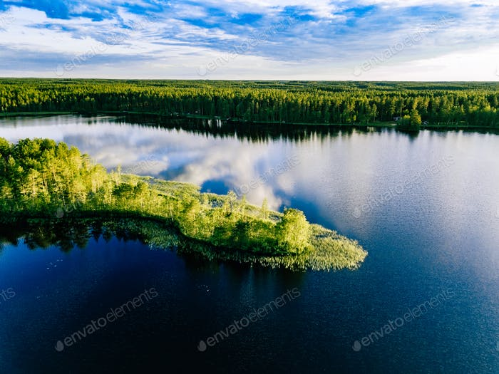 Aerial view of blue lakes landscape with green forests on a sunny summer day in Finland.