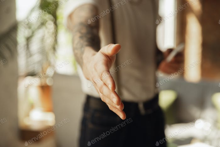 Close up of male hand greeting, welcoming somebody