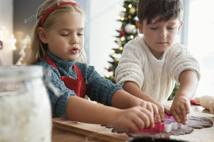 Two children cutting out gingerbread cookies