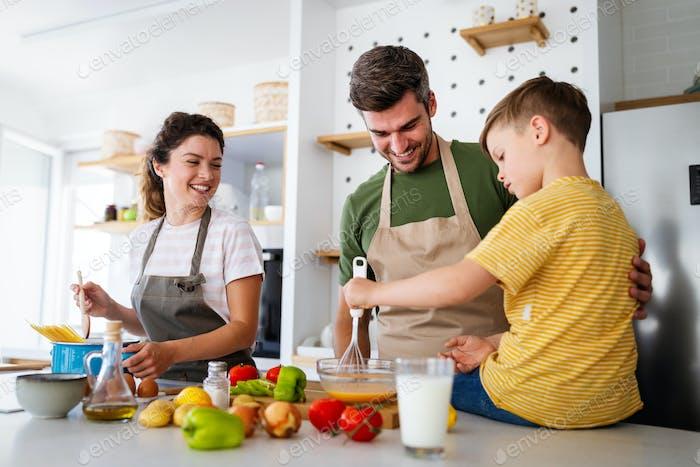 Glückliche Familie bereitet gemeinsam gesundes Essen in der Küche zu