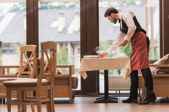 Side view of Waiter serving plates on a table at the restaurant